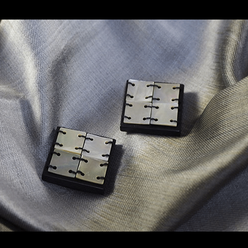 two square-shaped buttons on silk fabric